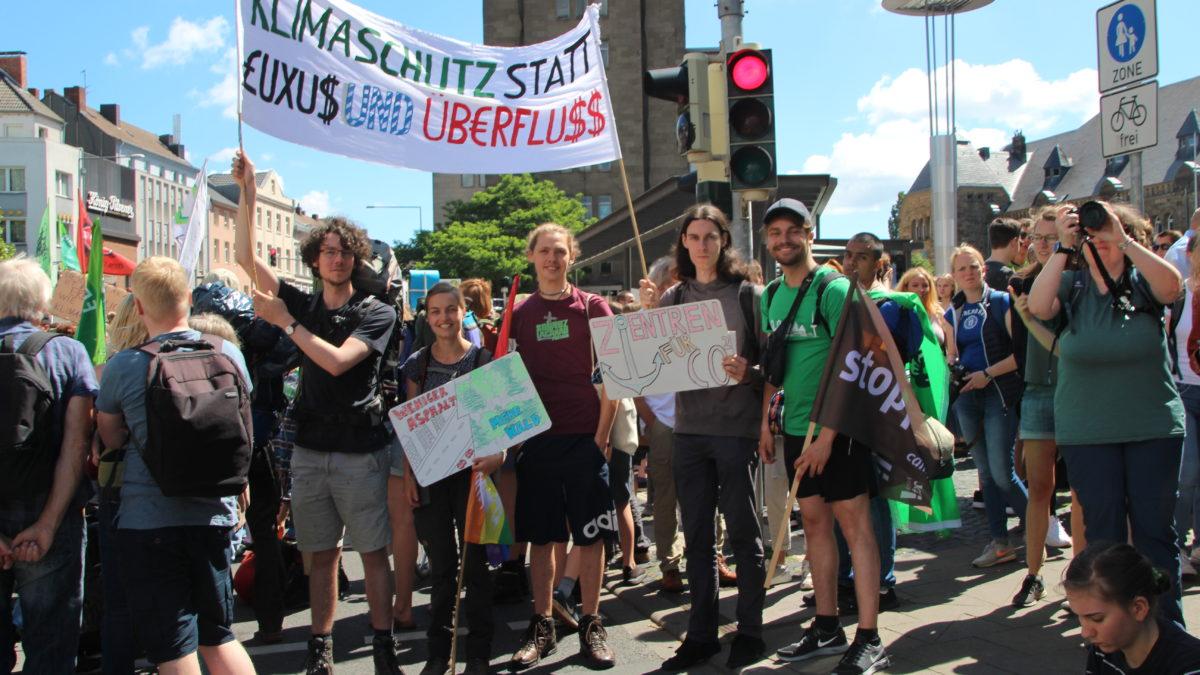 """Menschen des Kaktus auf einer Demo. Sie halten ein Plakat. Auf dem Plakat steht """"Klimaschutz statt Luxus und Überfluss""""."""