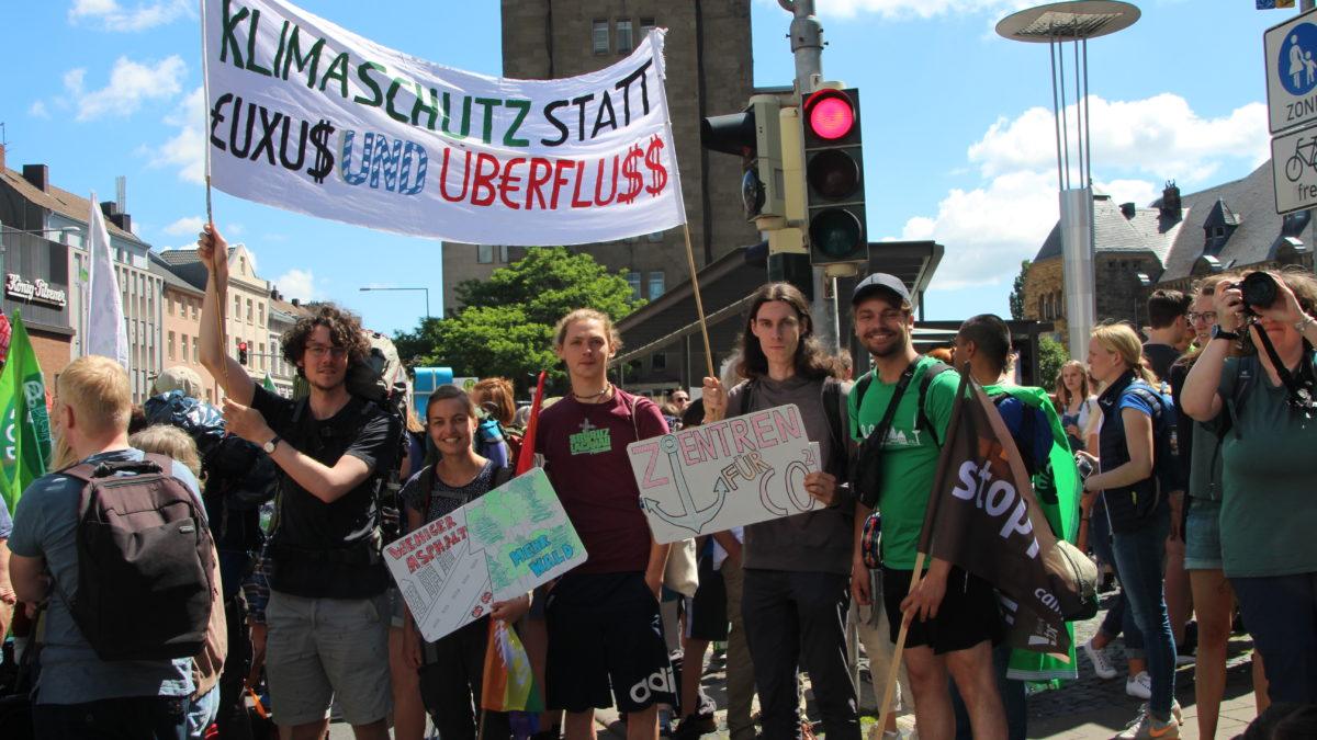 """Kaktus-Mitglieder auf einer Demo. Auf dem Plakat in ihrer Hand steht """"Klimaschutz statt Luxus und Überfluss""""."""