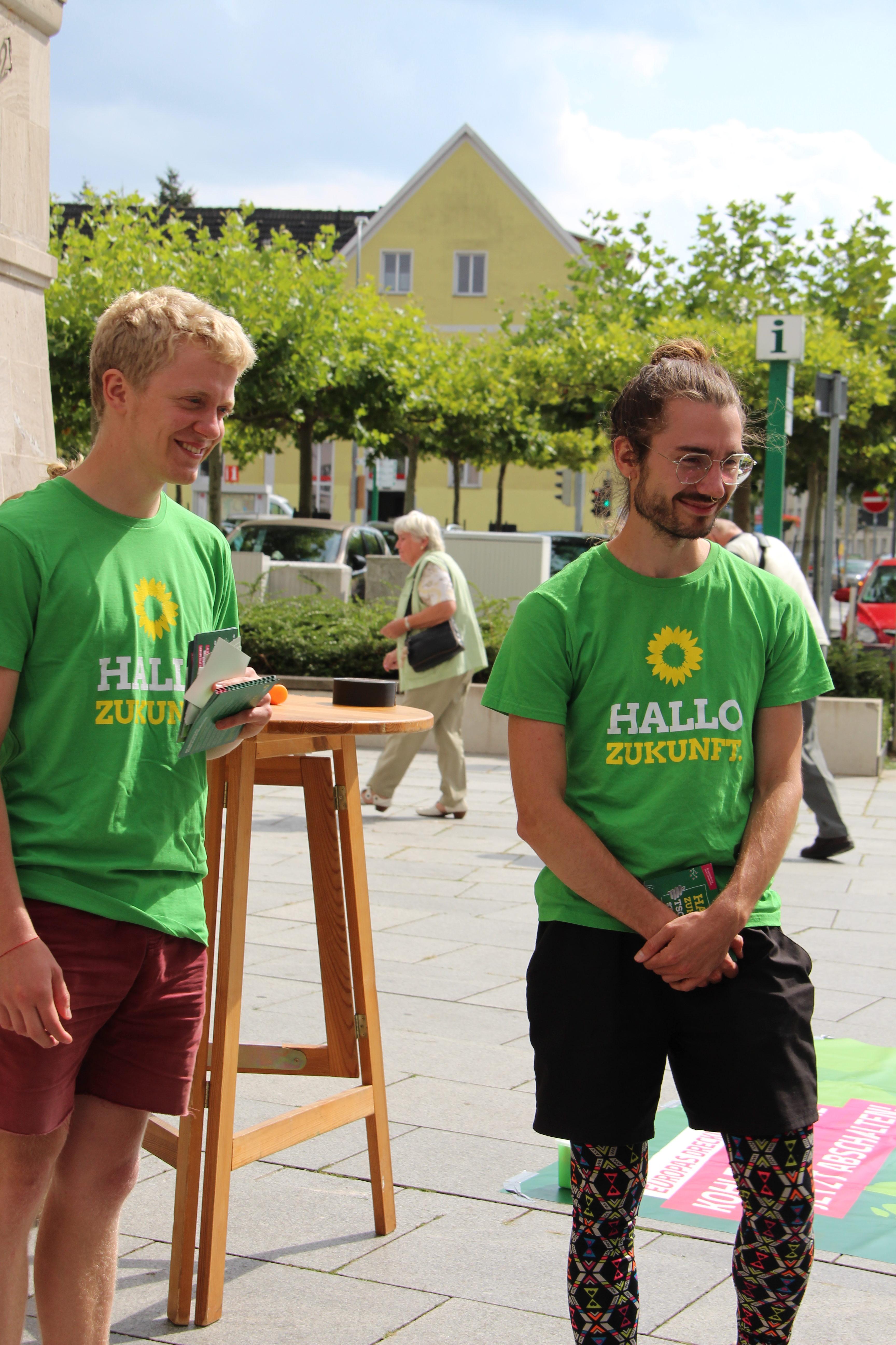 Zwei Menschen in Grünen T-Shirts stehen an einem Wahl·kampf·stand