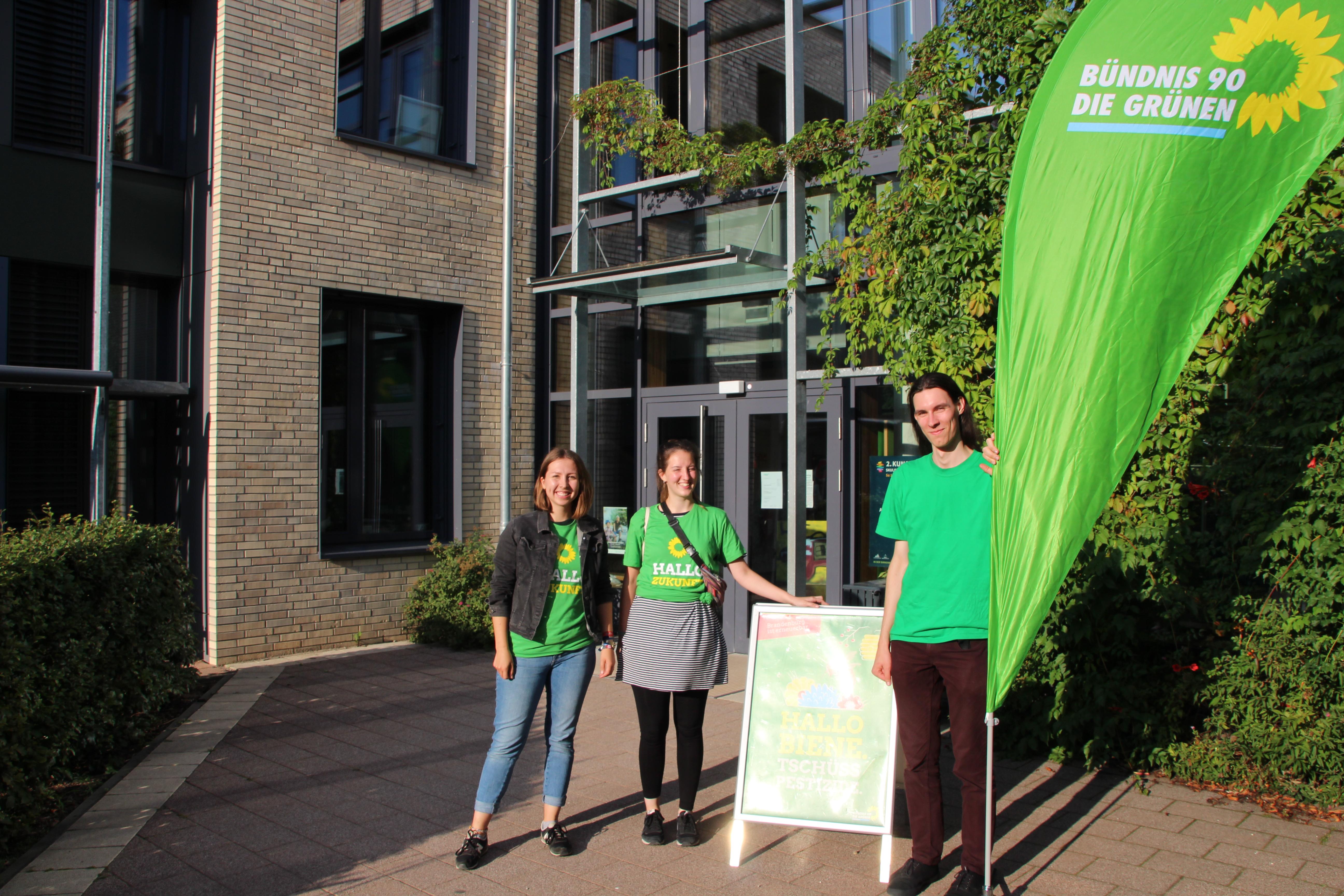 Drei Kakteen stehen neben einer Fahne der Grünen. Sie lachen in die Kamera.