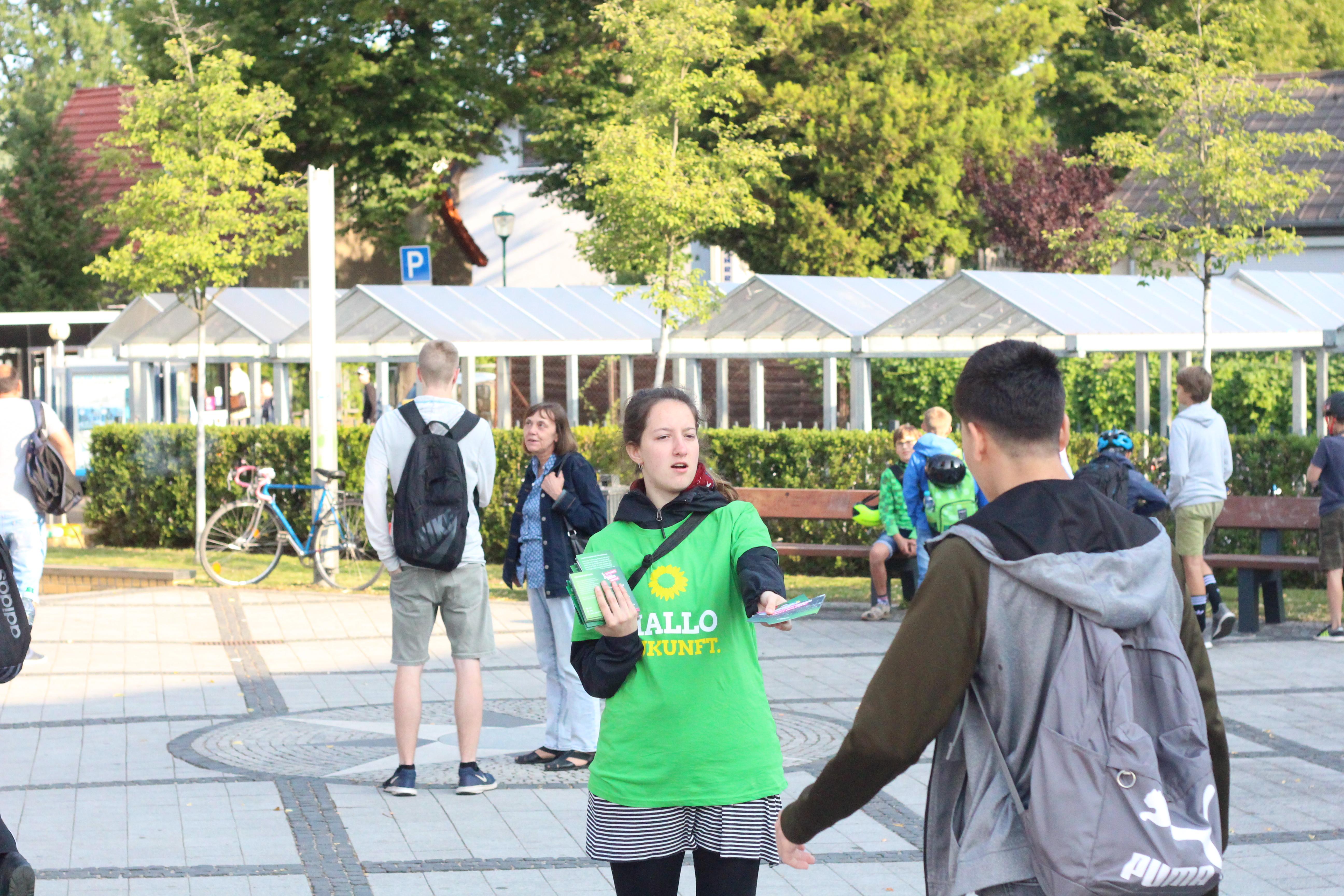 Eine Person mit einem T-Shirt der Grünen verteilt Informationen