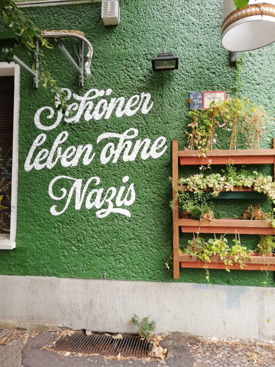 """Auf dem Bild ist eine grüne Wand. Auf der Wand steht: """"Schöner leben ohne Nazis."""""""