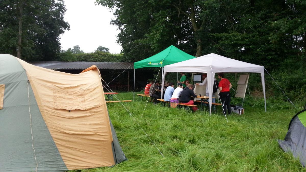 Menschen sitzen auf einer Wiese neben Zelten unter Pavillons und lauschen einem Vortrag.