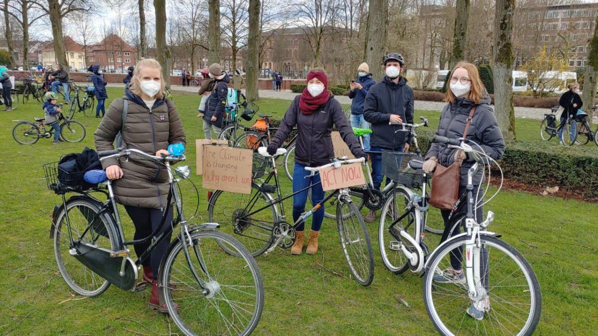 Menschen stehen mit Masken und Fahrrädern auf einer Wiese und schauen in die Kamera.