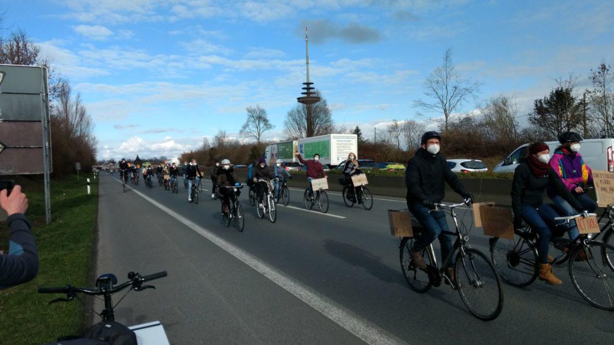 Menschen fahren mit ihren Fahrrädern über eine Bundesstraße. Manche winken. Auf der anderen Fahrbahn stehen Autos im Stau.
