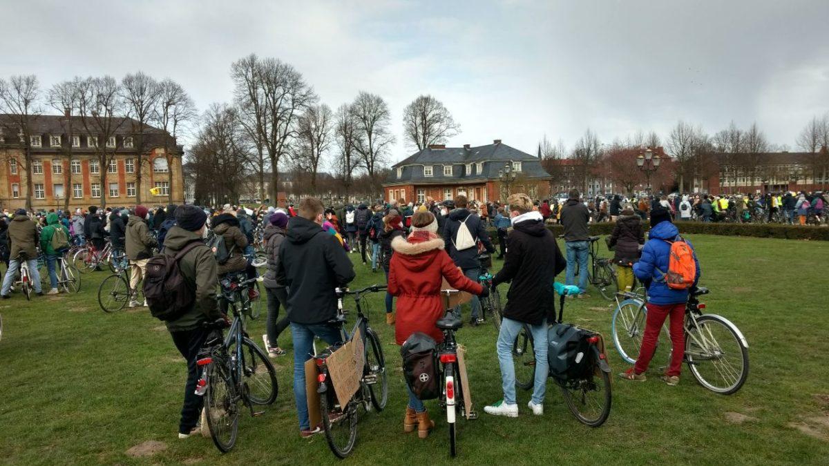 Viele Menschen stehen mit ihren Fahrrädern in einer Schlange. Sie unterhalten sich und warten