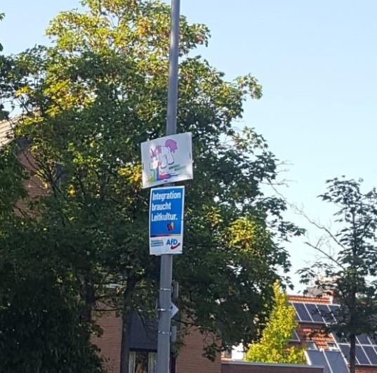 An einer Laterne hängt ein Plakat der AfD. Über dem Plakat hängt ein Plakat der Grünen Jugend Münster. Auf dem Plakat ist ein Einhorn, das einen Regenbogen nach unten auf das AfD-Plakat kotzt, zu sehen.