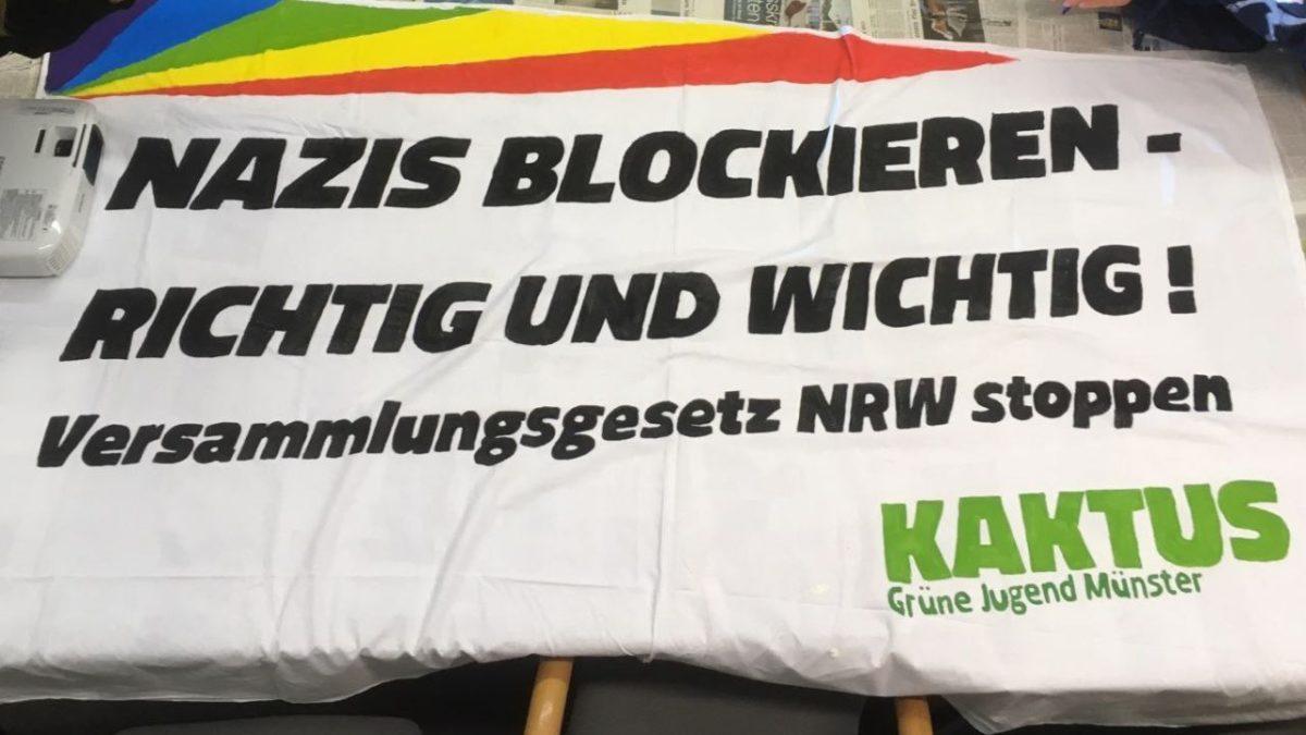 Ein Tuch liegt auf einem Tisch. Auf dem Tuch steht Nazis blockieren - richtig und wichtig. Nazis hassen andere Menschen. Weil sie aus einem anderen Land kommen. Das finden wir doof. Deshalb sind wir gegen Nazis.